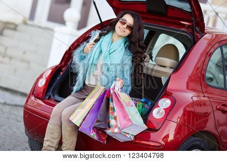 The young beautiful woman, the brunette with a long curly hair, in dark sun glasses, is dressed in a blue fur jacket, on a neck - a blue knitted scarf, left shopping center to the red car with color bags to load purchases into a luggage carrier ** Note: