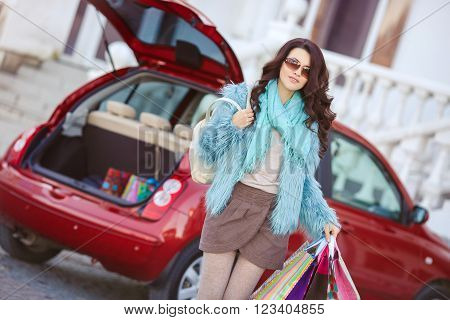 The young beautiful woman, the brunette with a long curly hair, in dark sun glasses, is dressed in a blue fur jacket, on a neck - a blue knitted scarf, left shopping center to the red car with color bags to load purchases into a luggage carrier