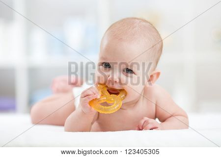 baby little child lying on bed weared diaper with teether