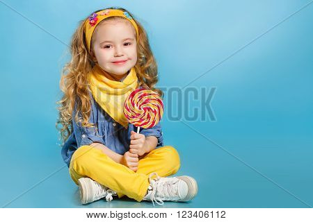 Funny little girl with long,curly red hair,with a yellow handkerchief around his neck,a sweet smile,is dressed in a blue shirt and yellow pants,posing in Studio sitting on the floor on a blue background holding a large,round,colourful Lollipop
