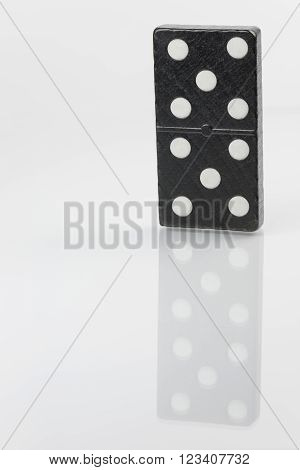 Standing black domino brick with white dots