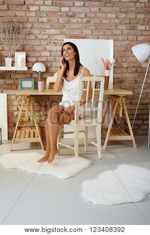 Attractive young woman talking on mobilephone at home, smiling happy, sitting on chair.