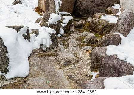 Watercourse over stone in winter with snow.