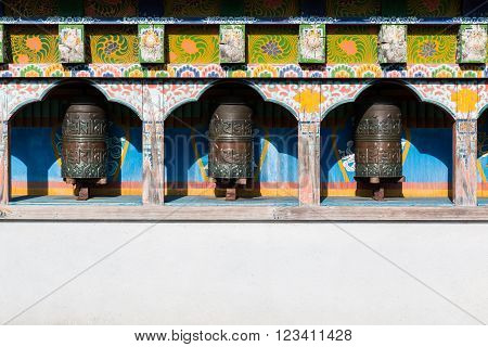 Buddhist three prayer wheels in Nepal with daylight.