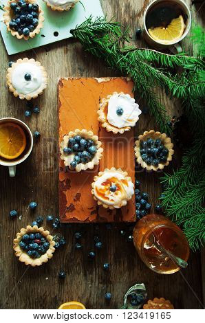 Tart with lemon curd and fresh blueberry, top view. Dessert tartlets with blueberries on  wooden background. Mini lime curd tartlets with meringue. Holiday concept. Top view.