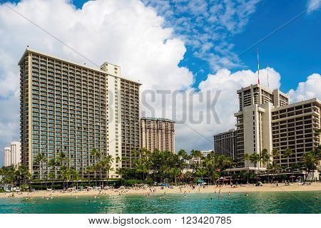 Waikiki, Honolulu, Hawaii, USA - December 13, 2015: Looking back at the Waikiki Beach area, from out at sea onboard a boat. Beach-goers can be seen enjoying the afternoon sun. Some hotels line the skyline.