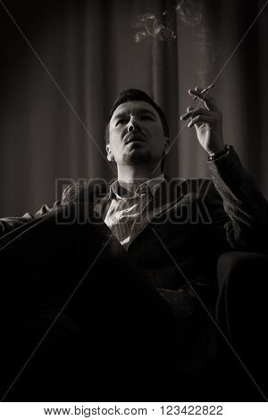 A pensive man smokes a cigar in the room