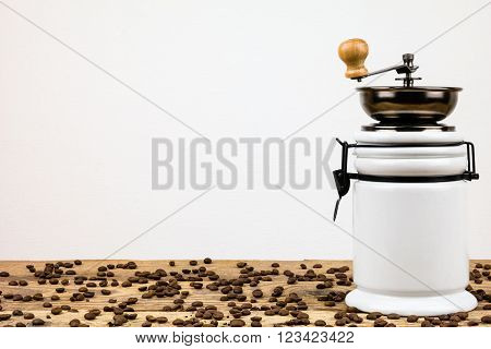 Vintage coffee grinder mill and beans on wooden table photographed over a white background. poster