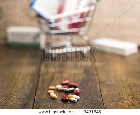Colorful pills with pill box and shopping cart on dark wooden background