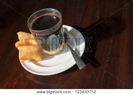 "Thai tradition hot coffee with sweetened condensed milk in old style cup served with deep fried dough or ""patongko"" in Thai word on wooden table. Thai style traditional breakfast. poster"