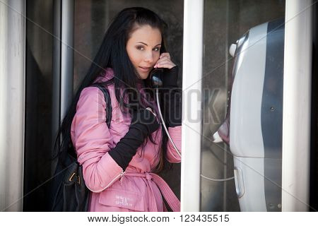 Girl in a jacket holding a pipe payphone
