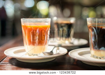 Thai tradition hot tea with sweetened condensed milk in old style cup served on wooden table. poster