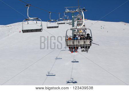 Skiers on the ski lift in Dolomiti Alps, Italy