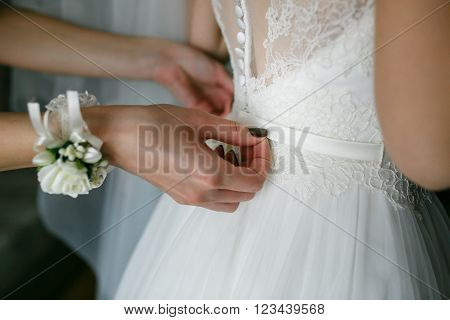 bridesmaid buttoning on corset bride's wedding dress