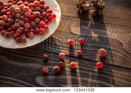 Frozen cranberry on wooden background close-up shot