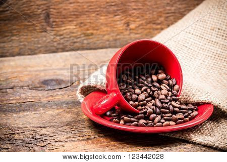 Red coffeecup and plate with spilled coffeebeans on gunny background