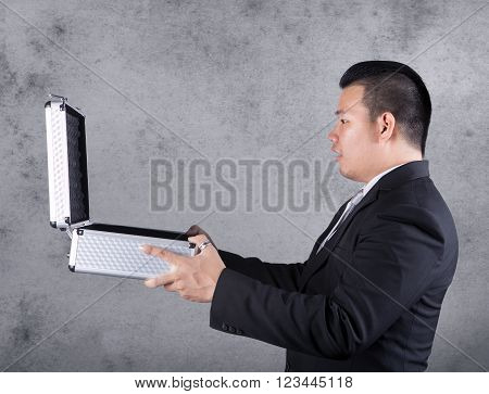 Business Man Open Metal Suitcase And Surprising Face Against Empty Cement Wall ,with Copy Space To F