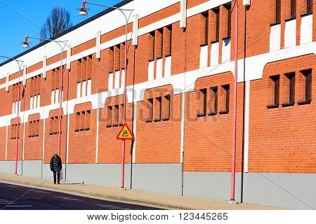 Ahus Sweden - March 20 2016: Architectural detail of the Absolut Company factory the place where Absolut Vodka is made. Red bricks with white details. Person walking outside.