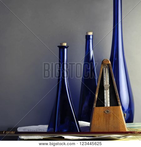 A retro metronome next to a fiddle stick and blue decorative bottles in the blurred background concept of music studio shot
