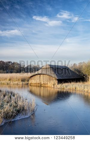 A wooden boathouse at Hickling Broad on a winters morning.