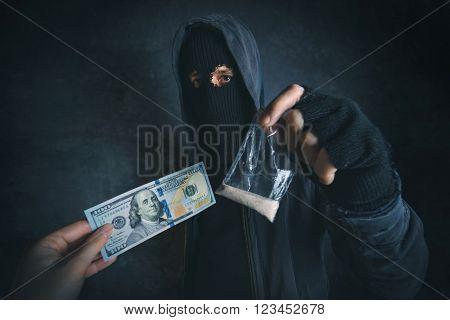 Drug dealer offering narcotic substance to addict on the street unrecognizable hooded criminal selling drugs in dark alley for dollar baknotes