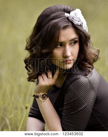Portrait of upset, unhappy, sorrowful, beautiful, attractive, pretty, nice girl, woman, model with wreath in the curly, brown, shiny, short hair, sitting in the park, thinking about something, worry about problems.