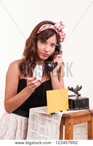 Fashion young woman with a retro look speaks at a vintage phone and looks at a bottle with medicine