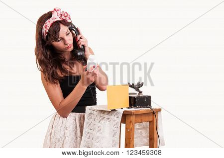 Fashion young woman with a retro look speaks at a vintage phone and reads from a bottle with medicine