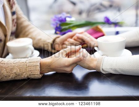 couple holding hands in a cafe. couple in love drinking coffee at a table in a cafe. hands closeup. side view