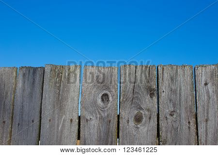 old wooden fence and a blue sky. wooden planks on a background of pure clear sky. front view. copy space for your text