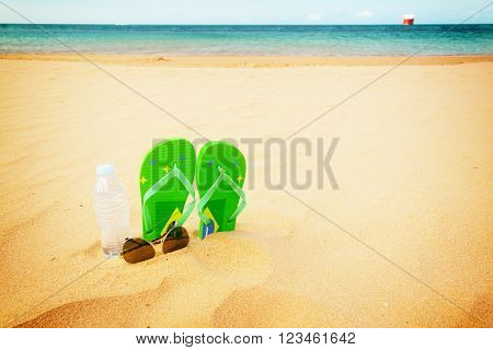 green  sandals  on  beach with bottle of clear water and glasses, retro toned