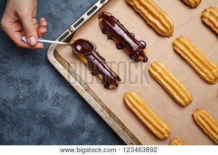 Eclairs or profiterole with chocolate and whipped cream preparing on baking sheet. Spreading chocolate on top of eclair with spoon. Traditional French dessert. Empty space for design text template.