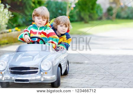 Two funny sibling kid boys playing with big old vintage toy car in spring or autumn garden, outdoors. Active leisure with kids outdoors  on warm spring or autumn day.