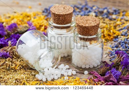 Bottles of homeopathy globules and dry healthy herbs on table. Selective focus.