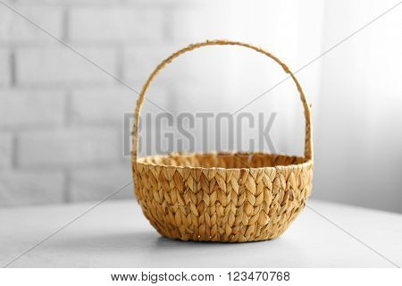 Wicker basket with handle on wooden table, closeup