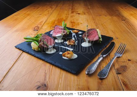 Sliced beef grilled beautifully decorated on a black plate. cutlery. Wooden table. radishes, broccoli, sauce.