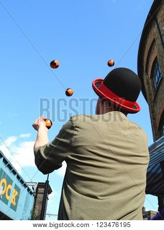 Juggler playing  with balls against blue sky