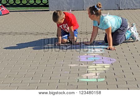 VORONEZH, RUSSIA - September 26, 2015: Pre-adolescent boy and girl enthusiastically chalking on the paving slabs of the city pond embankmen. September 26, 2015 in Voronezh, Russia