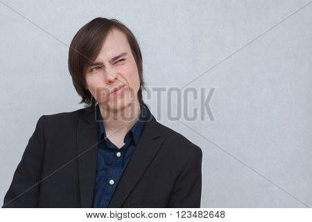 a young white man in a black jacket with a disgruntled look on his face