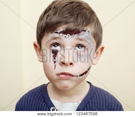 little cute boy with facepaint like zombie apocalypse at halloween party close up on white background