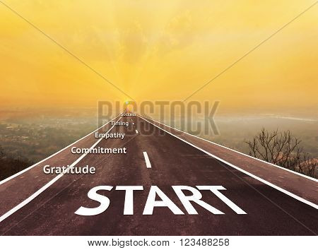Text start on long road aboved blurred top city view with text gratitude, commitment, empathy, timimg and success with sunrise background for business concept idea