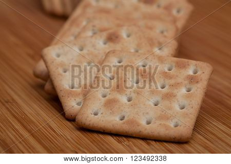 Dry square crackers on a wooden table