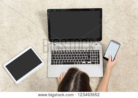 Woman working with multiple device screens lying on the floor at home