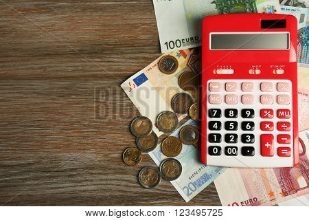 Money concept. Red calculator with banknotes and coins on wooden table