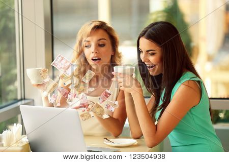 Financial concept. Make money on the Internet. Beautiful young women with laptop in cafe