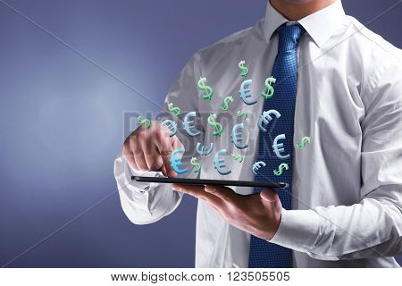 Making money online concept. Male hand touching screen tablet  with dollar and euro bills coming out, close-up