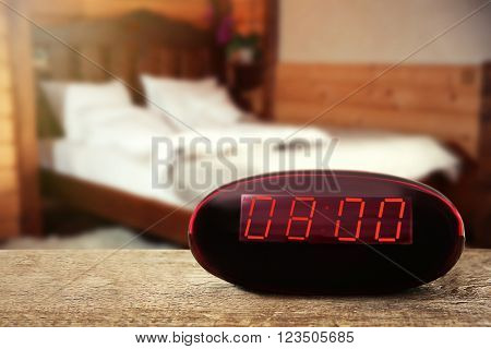 Digital clock showing 8:00 o'clock on wooden table, bedroom background