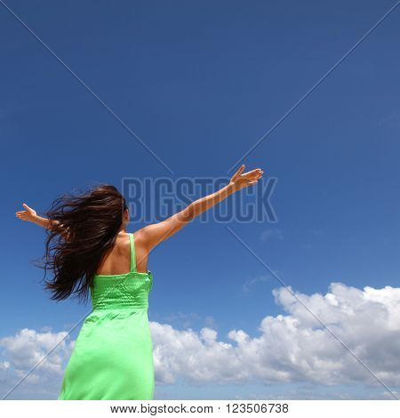 Woman with raised hands over blue sky background