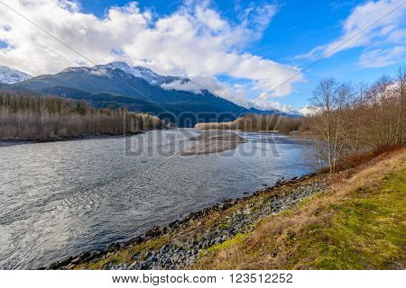 landscape with mountains trees and a river in front