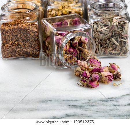 Front view of herbs and spices in glass jars with one jar spilling onto white marble stone. Selective focus on spilled rose buds.